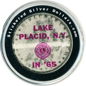 Sticker put on a Morgan silver dollar by the Lion's Club of Lake Placid, N.Y in 1965.